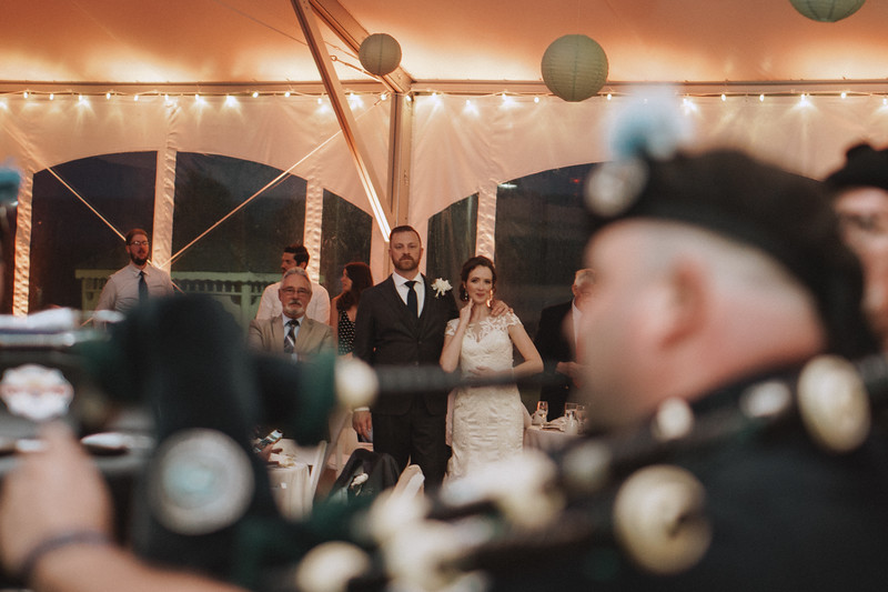 The bride smiles as she and the groom watch bag pipers perform.