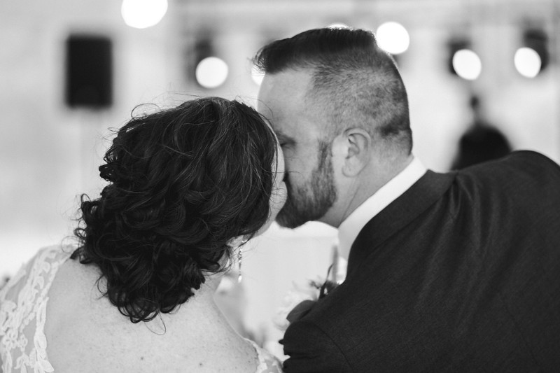 The bride and groom are seated next to one another and lean in for a kiss.