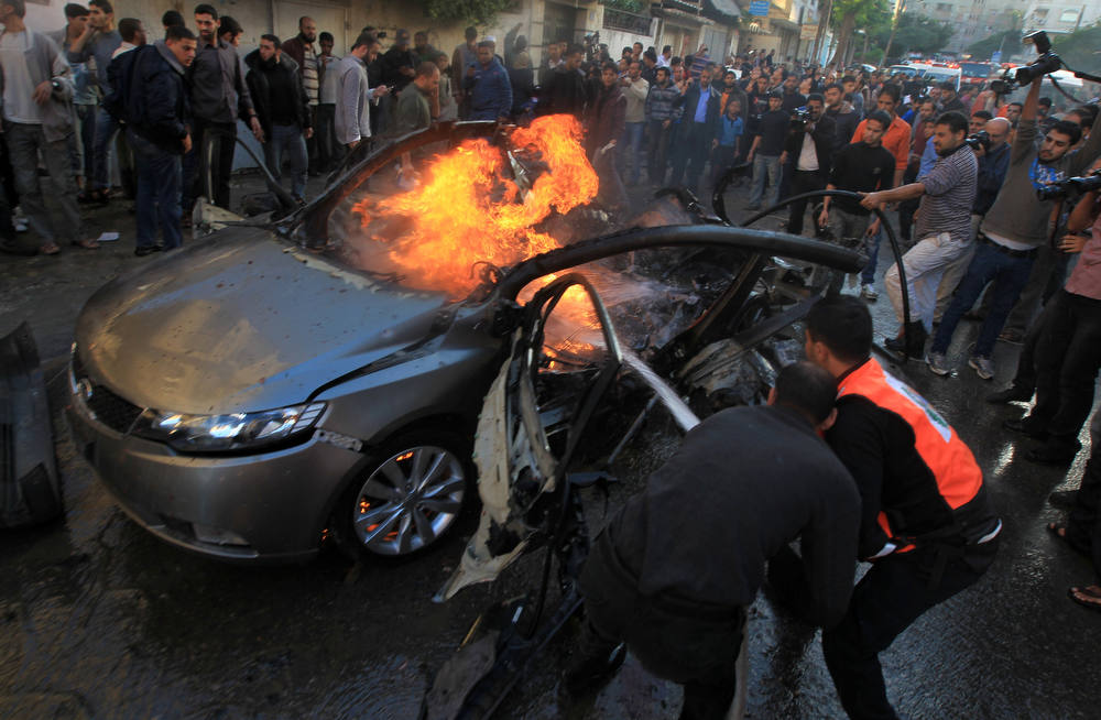 Description of . Palestinians extinguish fire from the car of Ahmed Jaabari,  head of the military wing of the Hamas movement, the Ezzedin Qassam Brigades, after it was hit by an Israeli air strike in Gaza City on November 14, 2012. The top Hamas commander Ahmed al-Jaabari was killed in an Israeli air strike , medics and a Hamas source told .   AFP PHOTO/MAHMUD  HAMS/AFP/Getty Images