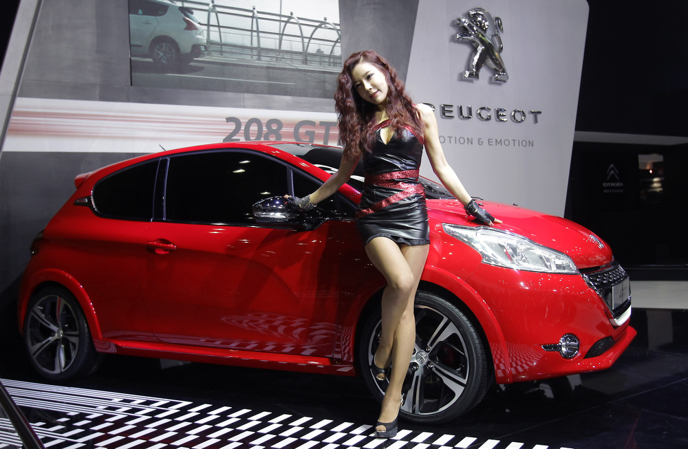 . A Model poses next to a PEUGEOT 208 GTi at the Seoul Motor Show 2013 on March 28, 2013 in Goyang, South Korea. The Seoul Motor Show 2013 will be held in March 29-April 7, featuring state-of-the-art technologies and concept cars from global automakers. The show is its ninth since the first one was held in 1995. About 384 companies from 14 countries, including auto parts manufacturers and tire makers, will set up booths to showcase trends in their respective industries, and to promote their latest products during the show.  (Photo by Chung Sung-Jun/Getty Images)