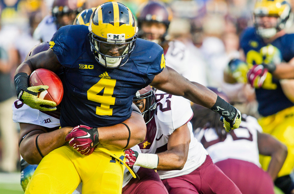 . Michigan running back De\'Veon Smith (4) tries to break away from Minnesota tackles in the second quarter of an NCAA college football game in Ann Arbor, Mich., Saturday, Sept. 27, 2014. (AP Photo/Tony Ding)