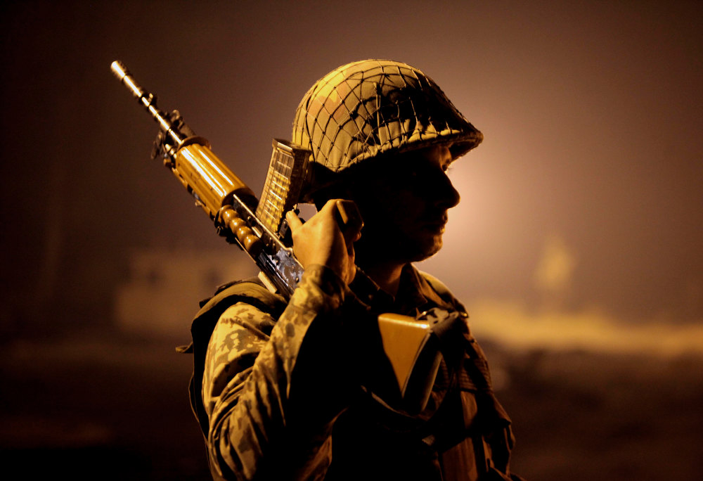 . An Indian Border Security Force (BSF) soldier stands guard during a night patrol near international border fencing at Suchet Garh in Ranbir Singh Pura, about 27 kilometers (17 miles) south of Jammu, India, Thursday, Jan. 10, 2013. The Pakistani army accused Indian troops of firing across the disputed Kashmir border and killing a soldier Thursday, the third deadly incident in the disputed Himalayan region in recent days. (AP Photo/Channi Anand)