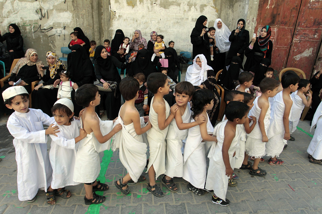 . Palestinian children, boys dressed in Ihram, specials outfits worn during the Hajj pilgrimage, stand in line in the yard of their school as they learn about Islam and how to perform the rituals carried out during the annual Hajj pilgrimage, at their Kindergarten in Rafah town in the southern Gaza Strip, on October 9, 2013. Muslims from around the world will flood the holy city of Mecca this week to perform the annual Hajj pilgrimage, which is one of the five pillars of Islam. SAID KHATIB/AFP/Getty Images