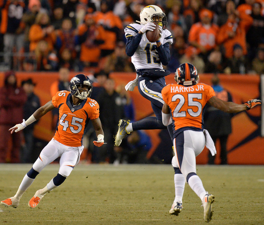 . San Diego Chargers wide receiver Keenan Allen (13) makes a catch between Denver Broncos cornerback Dominique Rodgers-Cromartie (45) and cornerback Chris Harris (25) during the second quarter. The Denver Broncos vs. the San Diego Chargers at Sports Authority Field at Mile High in Denver on December 12, 2013. (Photo by John Leyba/The Denver Post)
