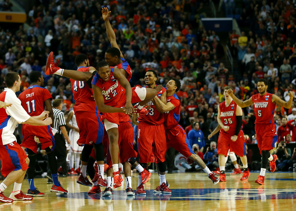 . The Dayton Flyers celebrate after defeating the Ohio State Buckeyes 60-59 in the second round of the 2014 NCAA Men\'s Basketball Tournament at the First Niagara Center on March 20, 2014 in Buffalo, New York.  (Photo by Elsa/Getty Images)
