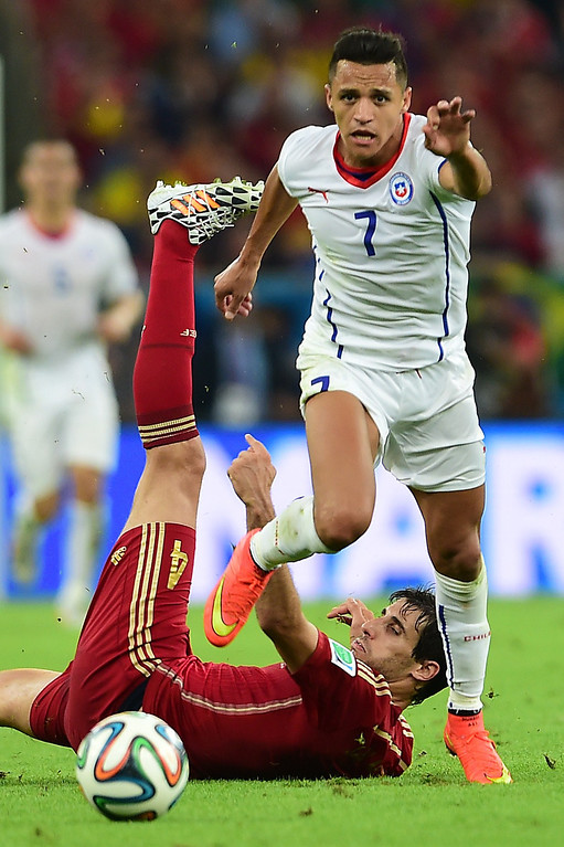 . Chile\'s forward Alexis Sanchez (top) and Spain\'s midfielder Javi Martinez vie for the ball during a Group B football match between Spain and Chile in the Maracana Stadium in Rio de Janeiro during the 2014 FIFA World Cup on June 18, 2014. MARTIN BERNETTI/AFP/Getty Images