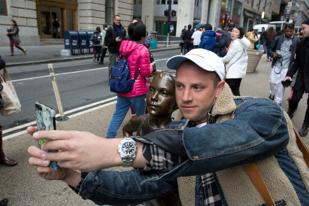 ". A man takes a photo with a statue of a fearless girl, Wednesday, March 8, 2017, in New York. The statue was installed by an investment firm in honor of International Women\'s Day. An inscription at the base reads, ""Know the power of women in leadership. She makes a difference. State Street Global Advisors.\"" (AP Photo/Mark Lennihan)"