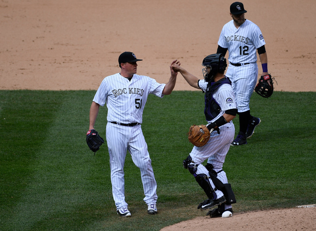 . DENVER, CO - MAY 11: Colorado Rockies relief pitcher Jake McGee (51) gets a fist bump form Colorado Rockies catcher Dustin Garneau (13) after his save over the Arizona Diamondbacks May 11, 2016 at Coors Field. The Colorado Rockies defeated the Arizona Diamondbacks 8-7.  (Photo By John Leyba/The Denver Post)