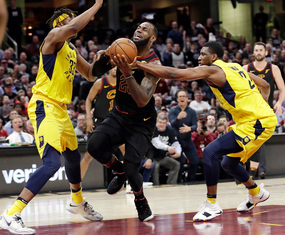 . Cleveland Cavaliers\' LeBron James, center, drives between Indiana Pacers\' Myles Turner, left, and Thaddeus Young during the first half of Game 2 of an NBA basketball first-round playoff series Wednesday, April 18, 2018, in Cleveland. (AP Photo/Tony Dejak)