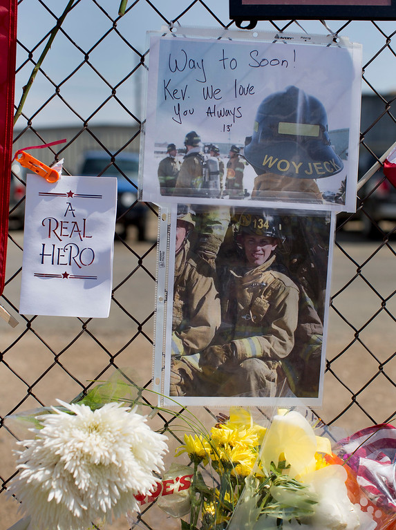 . A photo of Hotshot firefighter Kevin Woyjeck hangs on a fence outside the Granite Mountain Interagency Hotshot Crew fire station, Tuesday, July 2, 2013 in Prescott, Ariz. Woyjeck was one of 19 members of the Granite Mountain Hotshots, based in Prescott, who were killed Sunday when a windblown wildfire overcame them north of Phoenix.   (AP Photo/Julie Jacobson)