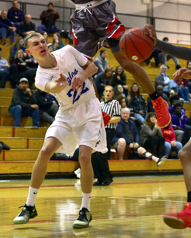 . Broomfield High School\'s Kip Mielke passes the ball under the hoop against Denver East during their game in the Fairview Festival on Wednesday. For More photos go to bocopreps.com Paul Aiken Staff Photographer Dec 6 2017