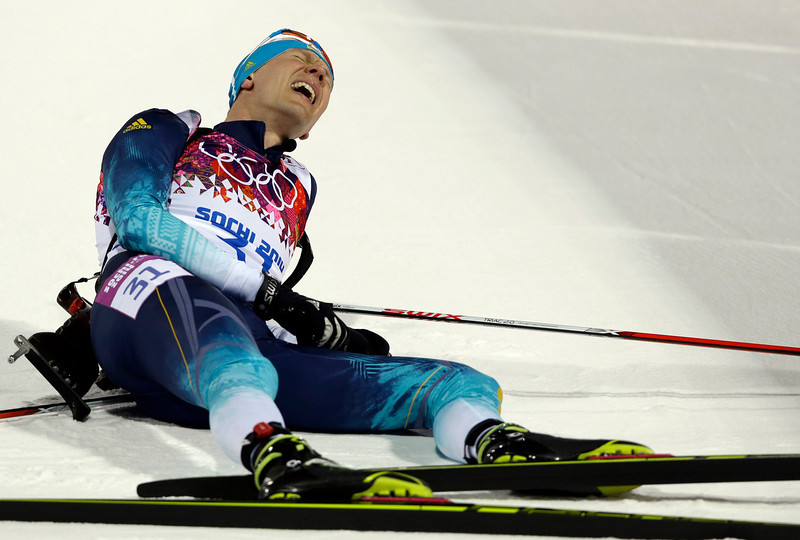 . Ukraine\'s Andriy Deryzemlya lies on the snow after completing the men\'s biathlon 10k sprint, at the 2014 Winter Olympics, Saturday, Feb. 8, 2014, in Krasnaya Polyana, Russia. (AP Photo/Kirsty Wigglesworth)