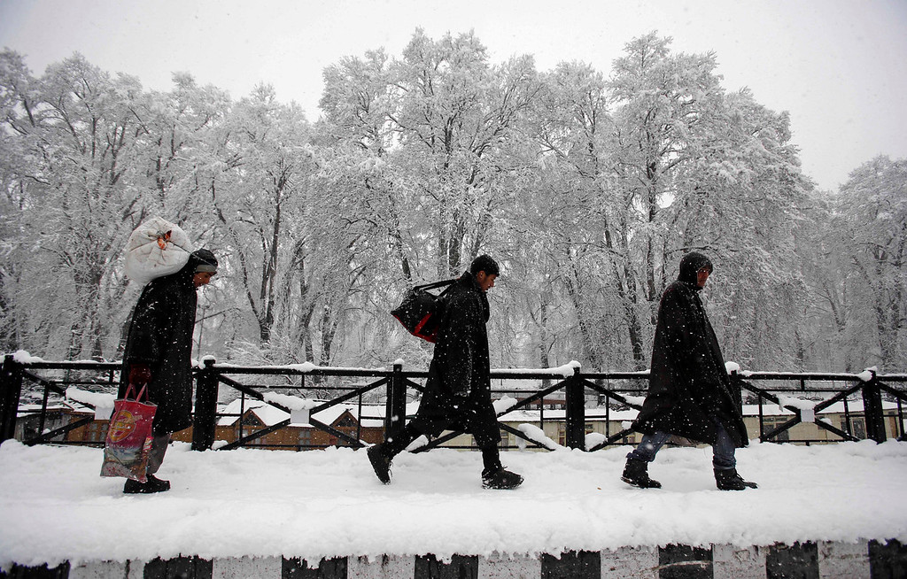 . Kashmiri men walk home luggage in hand after road and air traffic closed due to snowfall in Srinagar, India, Tuesday, Dec. 31, 2013. Snowfalls in the Indian portion of Kashmir has disrupted power supply,air traffic and road traffic between Srinagar and Jammu, the summer and winter capitals of India\'s Jammu-Kashmir state, according to news reports. (AP Photo/Mukhtar Khan)