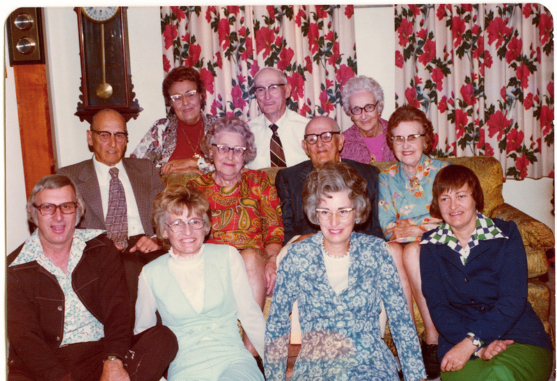 "Front Row Left to Right: Robert Edwin ""Ed"" Dew (1924-2006), Edna Ruth Dew (1925-2003), Donna Rogers Dew (1927-  ), Evelyn ""Evie"" Lois Dew (1929-2004), Middle Row Left to Right:  Burl Orville Dew (1904-2001), Mary Lavinna Dew (1895-1992), Perry Winfield Dew (1891-1975), Josie Louisa Dew (1897-1999)  Back Row Left to Right: Alice Martha Dew (1902-1999), Byron Elmer Dew (1893-1986), Glenna Ellen Dew (1900-1997) Written in the Rogers Reunion Photo Album Volume III page 21 above the photo ""The only time all 11 children of Wm Dew were together at the same time in their lives.  This was at Elmer's in Oregon, IL. September 20, 1975.  Front: Ed, Edna, Donna, & Evelyn. Center: Burl, Mary, Perry & Josie. Rear: Alice, Elmer & Glenna."""
