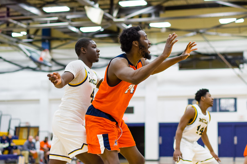 During the first half, MCLA's Bright Afful (4) tries to cut off the passing lane to Salem State's Hakeem Animashaun (24).