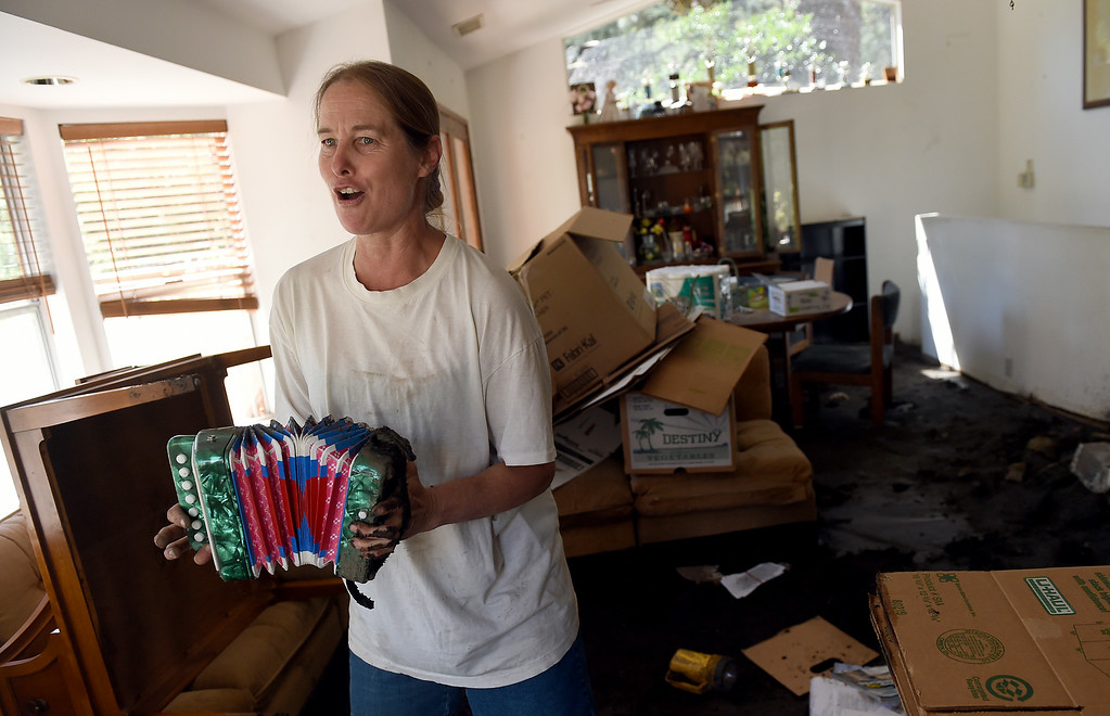 . Michelle Olson plays an accordian and sings about her red-tagged home as she tries to clean-up from Sunday\'s storm in Mt. Baldy, CA, Tuesday, August 5, 2014. (Photo by Jennifer Cappuccio Maher/Inland Valley Daily Bulletin)