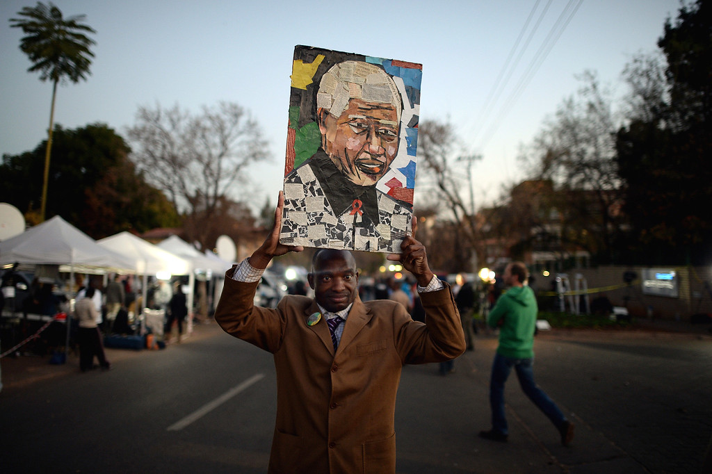 . PRETORIA, SOUTH AFRICA - JUNE 26: A man holds a picture as people gather to leave messages of support for former South African President Nelson Mandela outside the Mediclinic Heart Hospital June 26, 2013 in Pretoria, South Africa. South African President Jacob Zuma confirmed on June 23 that Mandela\'s condition has become critical since he was admitted to the hospital over two weeks ago for a recurring lung infection.  (Photo by Jeff J Mitchell/Getty Images)