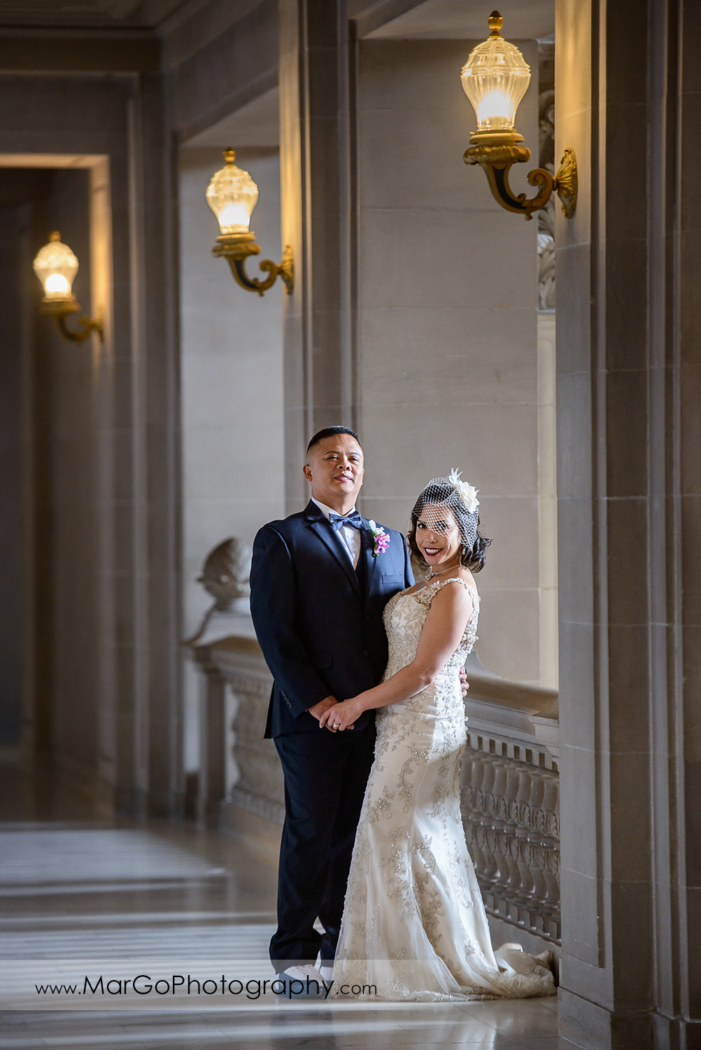 bride and groom standing at San Francisco City Hall