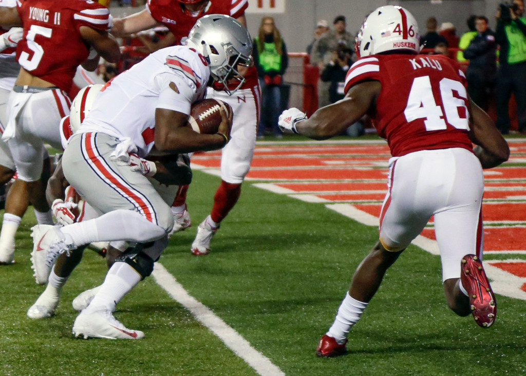 . Ohio State quarterback J.T. Barrett, left, crosses into the end zone for a touchdown in front of Nebraska defensive back Joshua Kalu (46) during the first half of an NCAA college football game in Lincoln, Neb., Saturday, Oct. 14, 2017. (AP Photo/Nati Harnik)