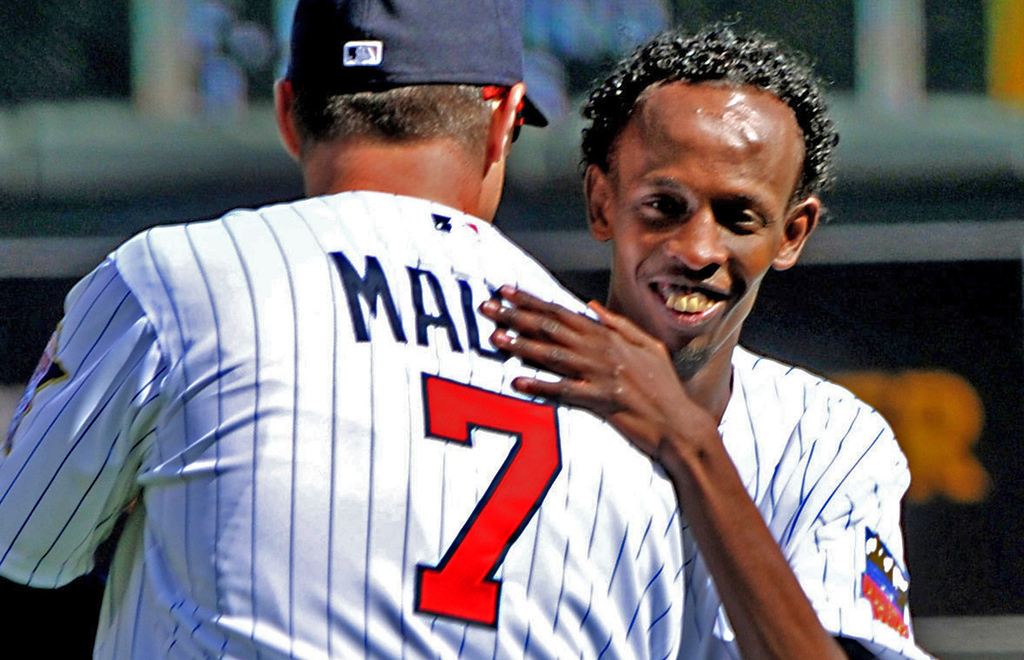 ". Barkad Abdi, star of the movie ""Captain Phillips,\"" hugs Twins first baseman Joe Mauer after Abdi threw out the ceremonial first pitch. (Pioneer Press: John Autey)"