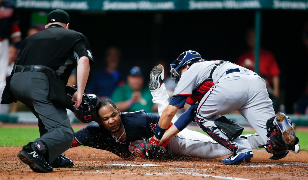 . Cleveland Indians\' Edwin Encarnacion, center, is tagged out at home plate by Minnesota Twins\' Jason Castro, right, as home plate umpire Todd Tichenor makes the call during the third inning in a baseball game, Tuesday, Sept. 26, 2017, in Cleveland. (AP Photo/Ron Schwane)