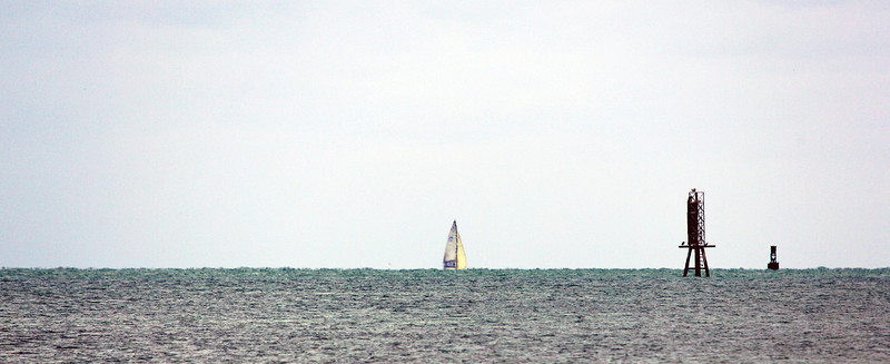 Distant sailboat disappearing over the horizon
