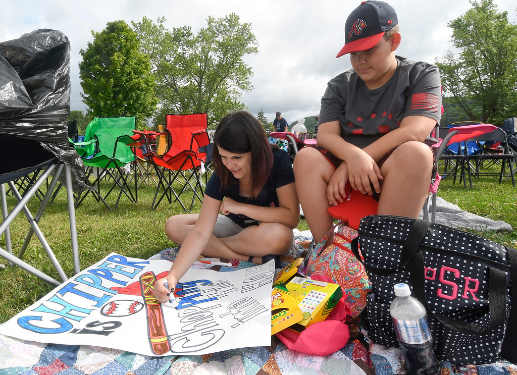 . Cicely Cable, left, and her nephew Sam Stewart, both of Andrews, N.C., work on a Chipper Jones poster before the start of National Baseball Hall of Fame induction ceremonies at the Clark Sports Center on Sunday, July 29, 2018, in Cooperstown, N.Y. (AP Photo/Hans Pennink)