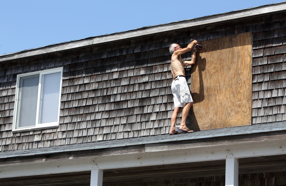 . Peter LeWando puts plywood sheets over the windows of the apartment where he lives  in Avon, N.C. on Thursday, July 3, 2014.  Hurricane Arthur is forecast to pass by Hatteras on Friday morning.  The island is under mandatory evacuation orders.  (AP Photo/The Virginian-Pilot, Steve Earley)