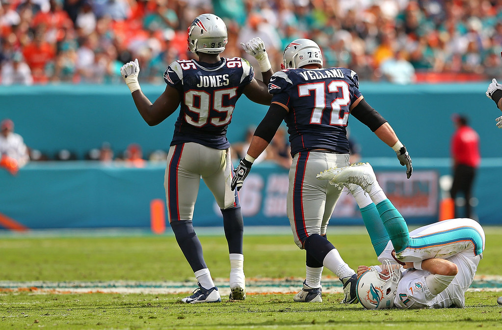 . Chandler Jones #95 and Joe Vellano #72 of the New England Patriots celebrate a sack on Ryan Tannehill #17 of the Miami Dolphins during a game  at Sun Life Stadium on December 15, 2013 in Miami Gardens, Florida.  (Photo by Mike Ehrmann/Getty Images)