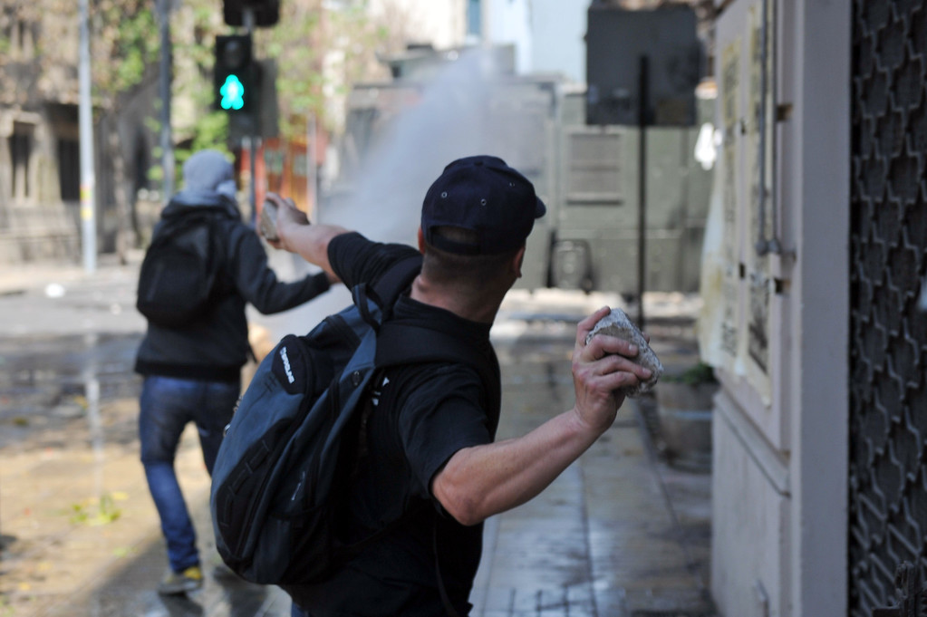. A man throws a stone to riot policemen during clashes after a march of Mapuche indigenous people in downtown Santiago, on October 12, 2013, during the commemoration of Columbus Day. HECTOR RETAMAL/AFP/Getty Images