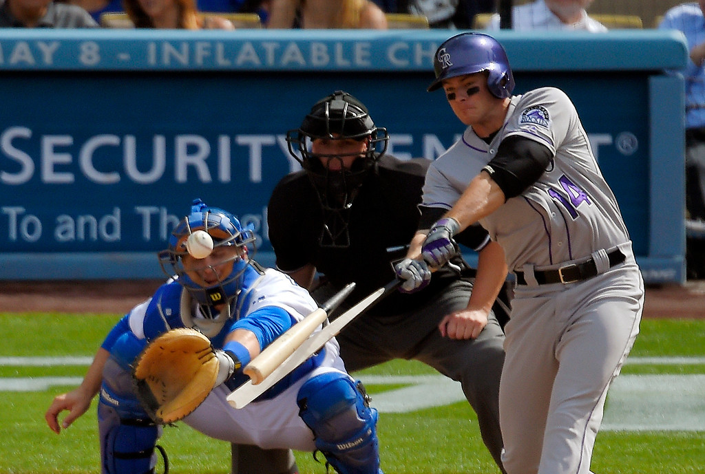 . Colorado Rockies\' Josh Rutledge, right, breaks his bat as Los Angeles Dodgers catcher Tim Federowicz catches during the eighth inning of a baseball game, Sunday, April 27, 2014, in Los Angeles. Josh Rutledge was safe at first on the play on an error by center fielder Matt Kemp. (AP Photo/Mark J. Terrill)