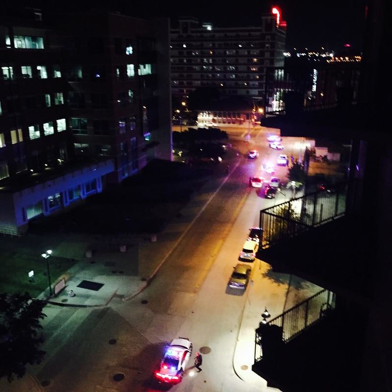 . In this handout photo provided by Anita Grendahl police respond moments after multiple shots were fired, early Saturday, June 13, 2015, in Dallas. Multiple gunmen toting automatic weapons opened fire on officers outside Dallas Police headquarters early Saturday morning, before one man fled the scene being chased by police in what witnesses described as an armored van, according to Dallas Police Chief David Brown. Anita Grendahl, via AP)