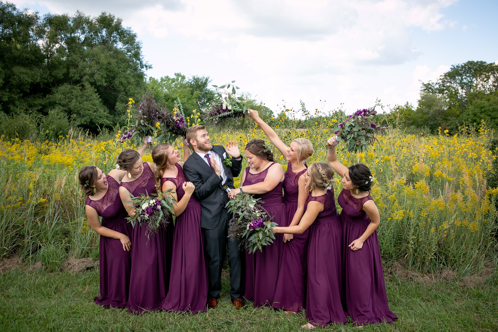 seven bridesmaids jokingly poking the groom with their bouquets