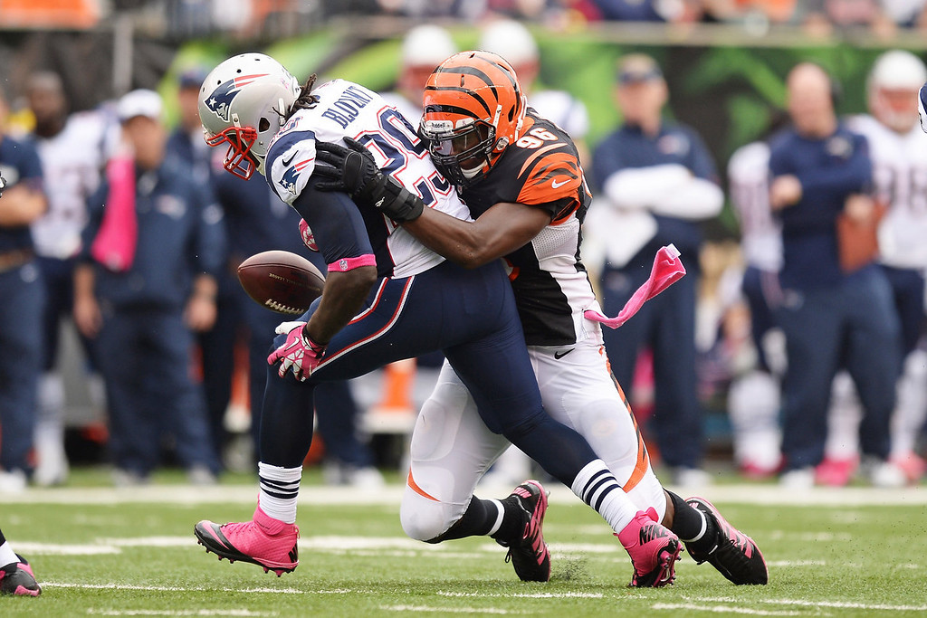 . Carlos Dunlap #96 of the Cincinnati Bengals forces LeGarrette Blount #29 of the New England Patriots to fumble after a short gain in the second quarter at Paul Brown Stadium on October 6, 2013 in Cincinnati, Ohio. Cincinnati recovered the fumble.  (Photo by Jamie Sabau/Getty Images)