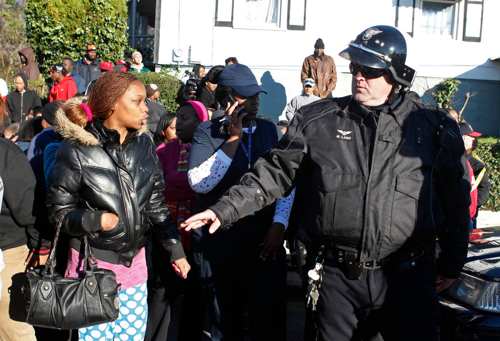 Description of . A parent exchanges words with a police officer as they stand waiting for students to be released at the entrance to Price Middle School following a shooting at the school in Atlanta, Georgia, January 31, 2013.   One student was shot and another arrested in the latest string of school shootings.   REUTERS/Tami Chappell