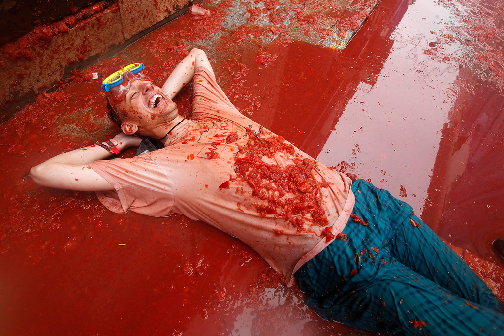 """. A man lies on a puddle of tomato during the annual \""""tomatina\"""" tomato fight fiesta in the village of Bunol, 50 kilometers outside Valencia, Spain, Wednesday, Aug. 28, 2013. Thousands of people are splattering each other with tons of tomatoes in the annual \""""Tomatina\"""" battle in recession-hit Spain, with the debt-burdened town charging participants entry fees this year for the first time. Bunol town says some 20,000 people are taking part in Wednesday\'s hour-long street bash, inspired by a food fight among kids back in 1945. Participants were this year charged some 10 euros ($13) to foot the cost of the festival. Residents do not pay. (AP Photo/Alberto Saiz)"""