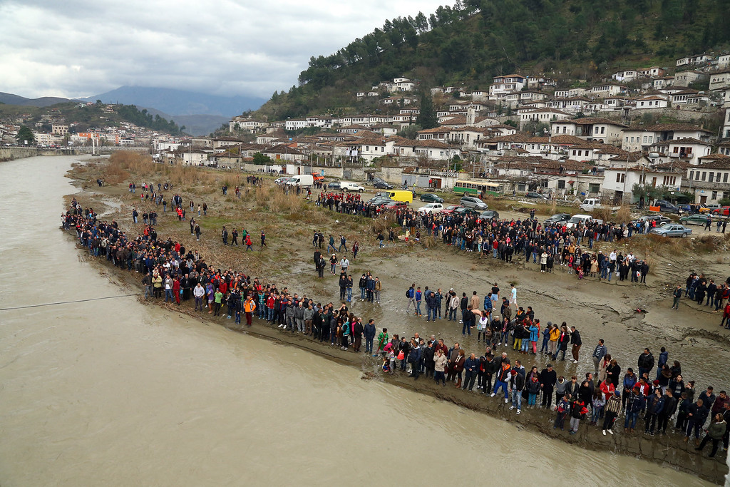 . View of the people gathered  in the southern city of Berat to watch an Eastern Orthodox priest throw a cross in the Osum River to celebrate Epiphany day as people believe that the one who retrieves it will be healthy through the year, Wednesday, Jan. 6, 2016. Albania is known for its religious coexistence where the Orthodox and Catholic communities live in peace with the majority Muslims.  (AP Photo/Hektor Pustina)