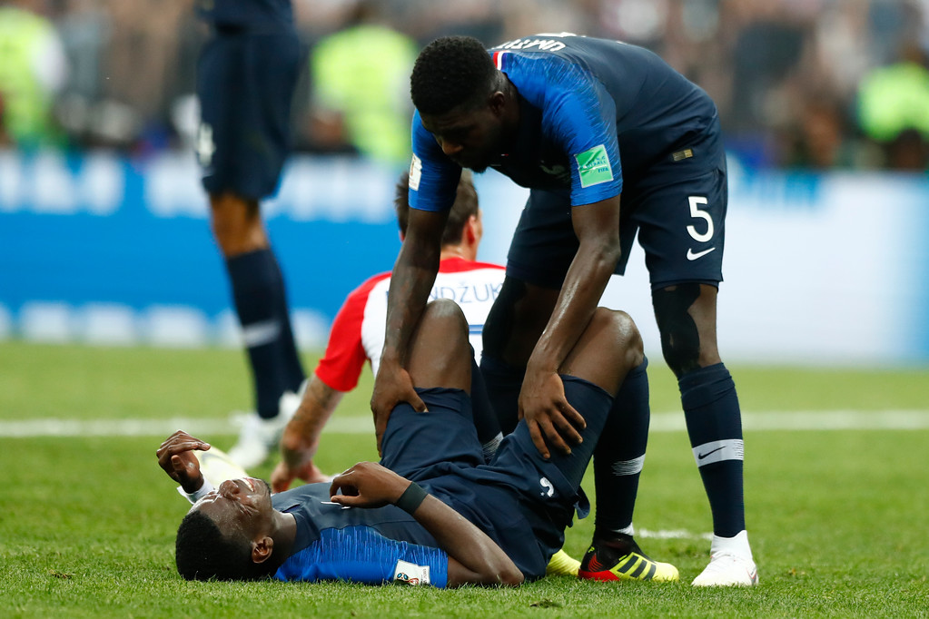 . France\'s Samuel Umtiti, top, assists France\'s Paul Pogba during the final match between France and Croatia at the 2018 soccer World Cup in the Luzhniki Stadium in Moscow, Russia, Sunday, July 15, 2018. (AP Photo/Matthias Schrader)