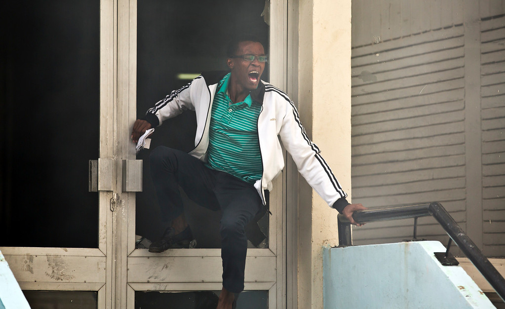 . A student or member of university staff tries to escape from a tear-gas-filled building, before being chased back inside by riot police, inside Nairobi University\'s main campus in downtown Nairobi, Kenya,  Tuesday, May 20, 2014. Kenyan university students on Tuesday carried out demonstrations over a proposed increase in student fees, but the protests quickly turned into hours of running battles between students throwing rocks and security forces firing tear gas, before riot police chased the students inside their campus and cornered them in a building into which they fired dozens of tear gas grenades and for a while prevented anyone from leaving. (AP Photo/Ben Curtis)