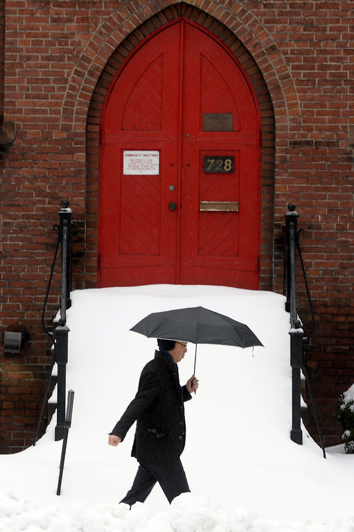 . A pedestrian walks through thick snow while passing a church door in Washington DC, USA, 13 February 2014. The Washington DC area was pounded by a snowstorm, with accumulation expected to reach twelve inches in some areas, as the storm moved up the mid-Atlantic to the Northeast region of the US.  EPA/MICHAEL REYNOLDS
