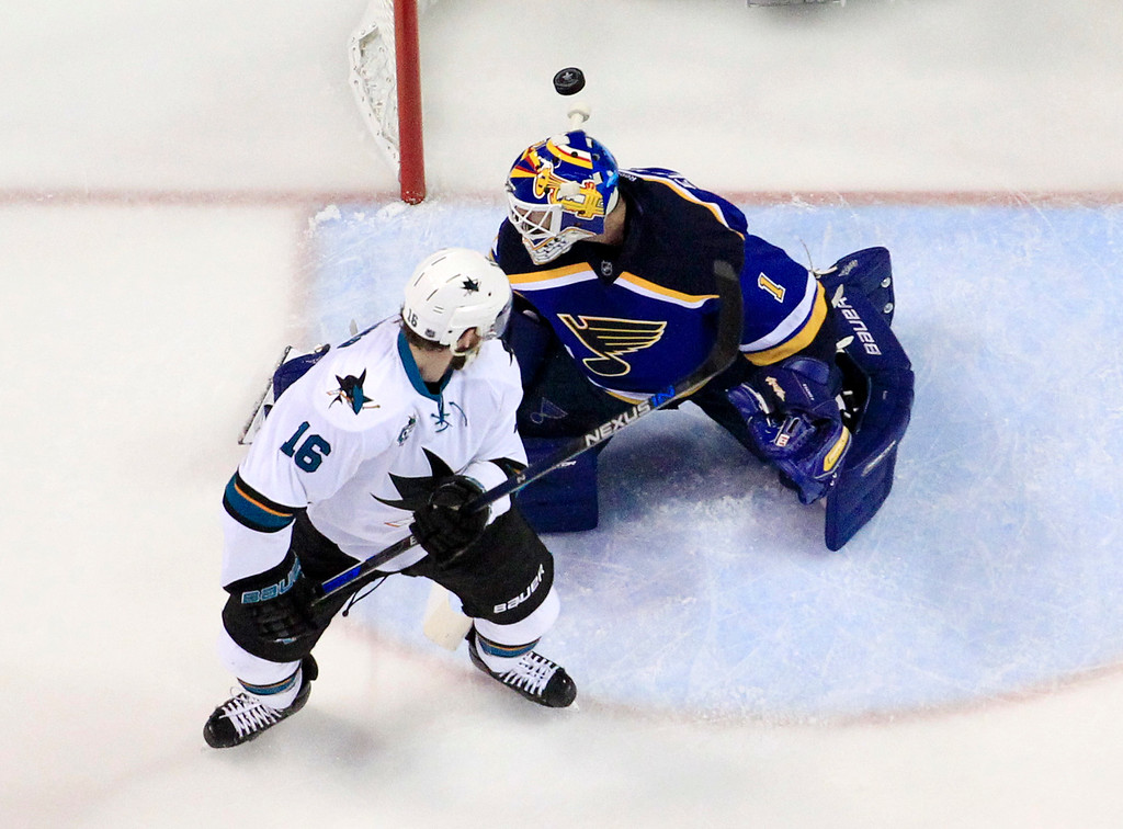 . San Jose Sharks center Nick Spaling (16) watches the puck as his teammate center Tommy Wingels (57) scores a shot against St. Louis Blues goalie Brian Elliott (1) during the first period in Game 2 of the NHL hockey Stanley Cup Western Conference finals, Tuesday, May 17, 2016, in St. Louis. (AP Photo/Jeff Roberson)