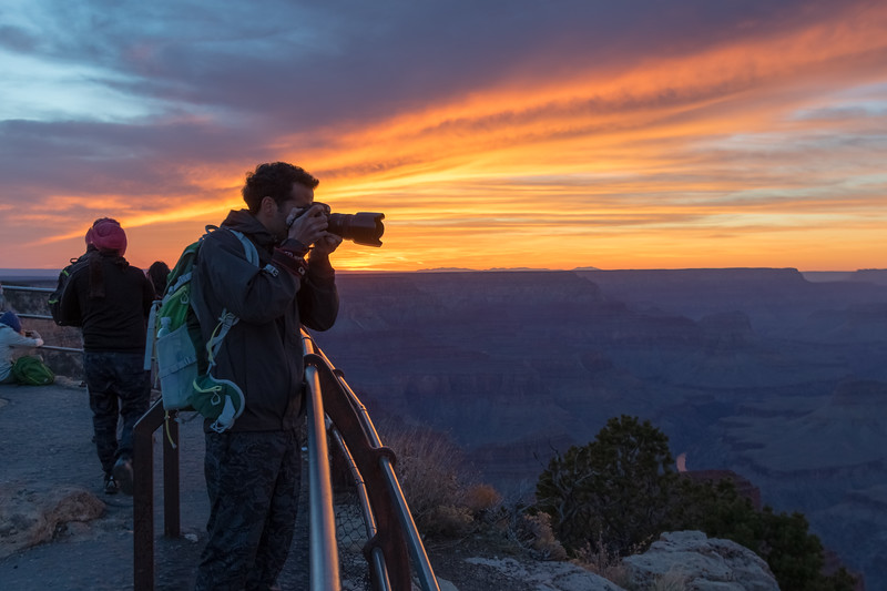 A photographer aims their camera over the Grand Canyon as the setting sun lights up distant clouds