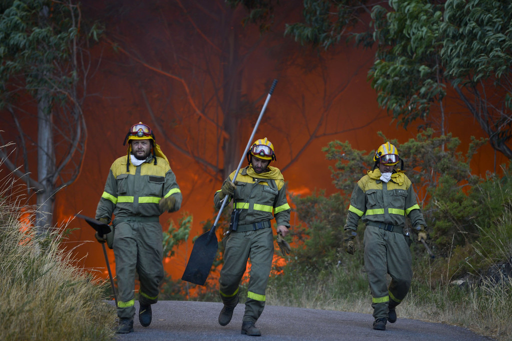 . Flames rise into the air as a firefighters work at the site of a wildfire in Lousame, near A Coruna, on August 29, 2013. Spain is prone to forest fires in summer because of soaring temperatures, strong winds and dry vegetation. Last year wildfires destroyed some 150,000 hectares of land in Spain from January to July, after one of the driest winters on record.   PEDRO ARMESTRE/AFP/Getty Images