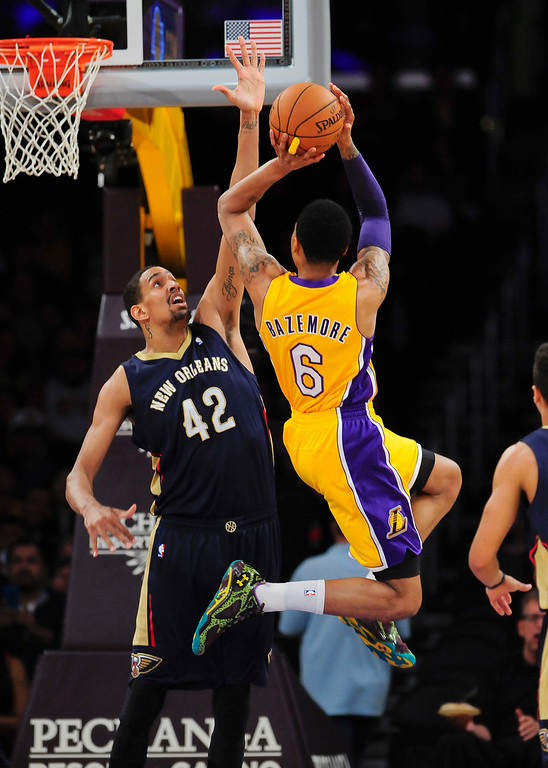. New Orleans Pelicans center Alexis Ajinca (42) attempts to block a shot from Los Angeles Lakers guard Kent Bazemore (6) in the first half of an NBA basketball game, Tuesday, March 4, 2014, in Los Angeles.(AP Photo/Gus Ruelas)