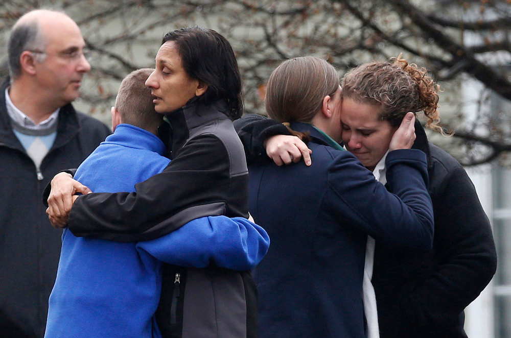 Description of . Mourners embrace as they leave the Honan Funeral Home, where the family of six-year-old Jack Pinto is holding his funeral service, in Newtown, Connecticut December 17, 2012. Pinto was one of the 20 students killed in the December 14 shootings at Sandy Hook Elementary School in Newtown. REUTERS/Mike Segar