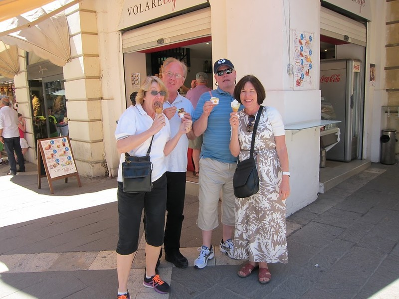 four boomer-aged people enjoying an icecream on the streets