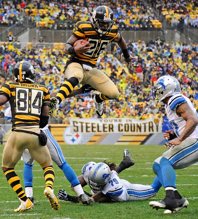 . Le\'Veon Bell #26 of the Pittsburgh Steelers jumps to avoid a tackle by Willie Young #79 of the Detroit Lions on November 17, 2013 at Heinz Field in Pittsburgh, Pennsylvania.  (Photo by Joe Sargent/Getty Images)