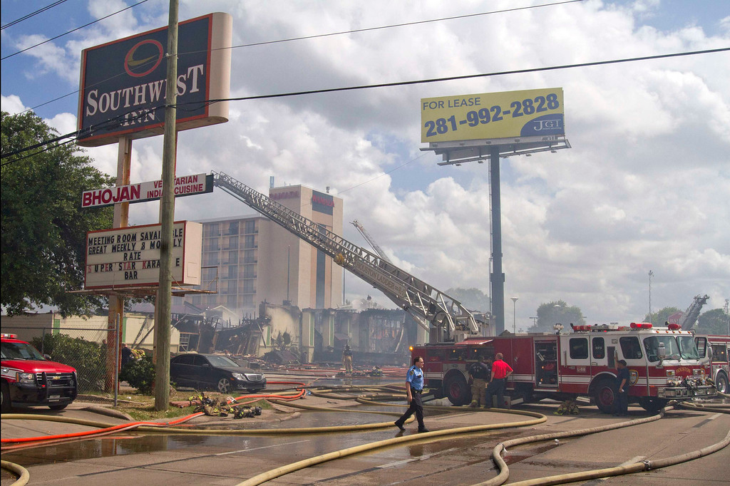 . Firefighters and police work the scene of a five-alarm fire at the Southwest Inn restaurant and hotel where at least six firefighters were injured, two of them critically, in southwest Houston May 31, 2013.     REUTERS/Richard Carson