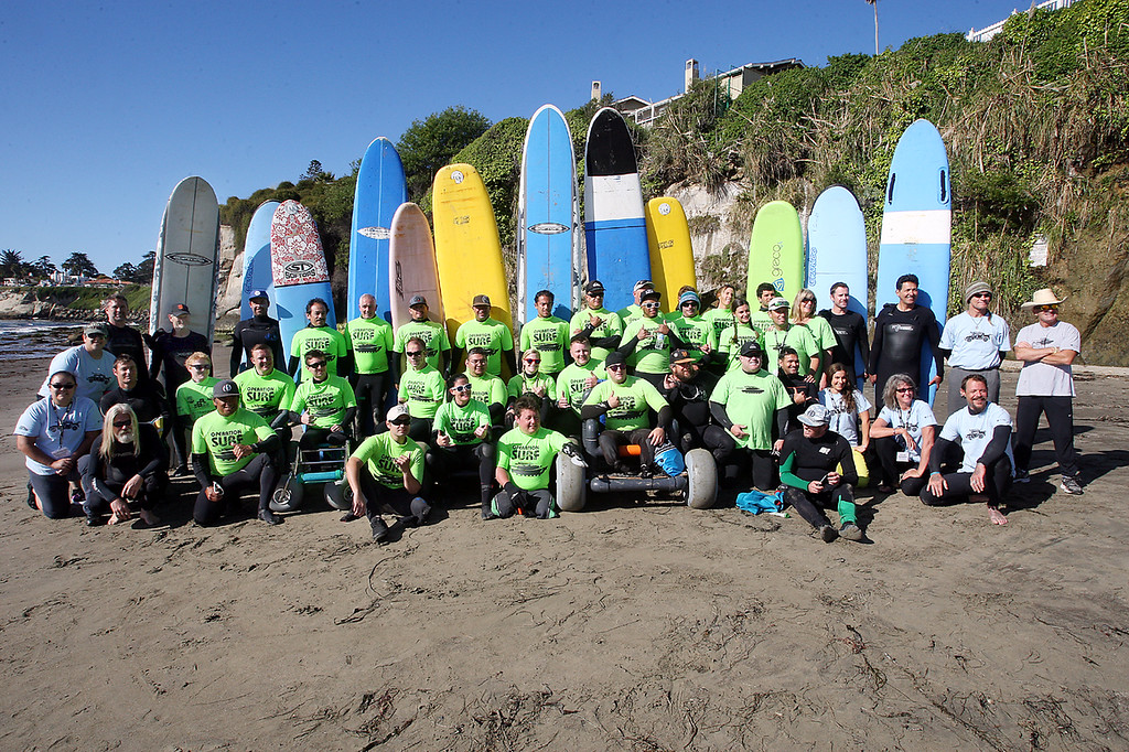 . Ten wounded soldiers and their surf instructors, staff and therapists with Operation Surf pose for a photo before the morning surf session at Cowell Beach in Santa Cruz, Calif., Tuesday, April 16, 2013.  (Dan Coyro/Sentinel)
