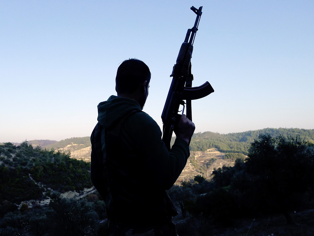 """. A member of the Free Syrian Army (FSA) looks at the valley in the village of Ain al-Baida, in the Idlib province of Syria, not far from the Turkish border, on December 15, 2011. A rebel group of Syrian defectors reportedly took position against the Syrian Army along the Turkish border. Army defectors killed at least eight Syrian troops on December 14 in an act of revenge after security forces shot dead five civilians, activists said, in the second such insurgent attack in as many days. \""""At least eight soldiers were killed in an ambush on four military jeeps travelling in the village of Al-Asharna on the outskirts of (the central city of) Hama,\"""" said the Britain-based Syrian Observatory for Human Rights.  The violence comes amid diplomatic wrangling, as Western nations seek tough action against Syria at the UN Security Council, where the regime of President Bashar al-Assad has support from his veto-wielding ally Russia. SEZAYI ERKEN/AFP/Getty Images"""